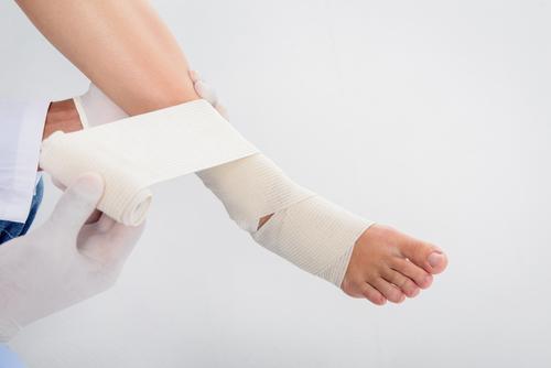 Врач бинтует ногу пациенту