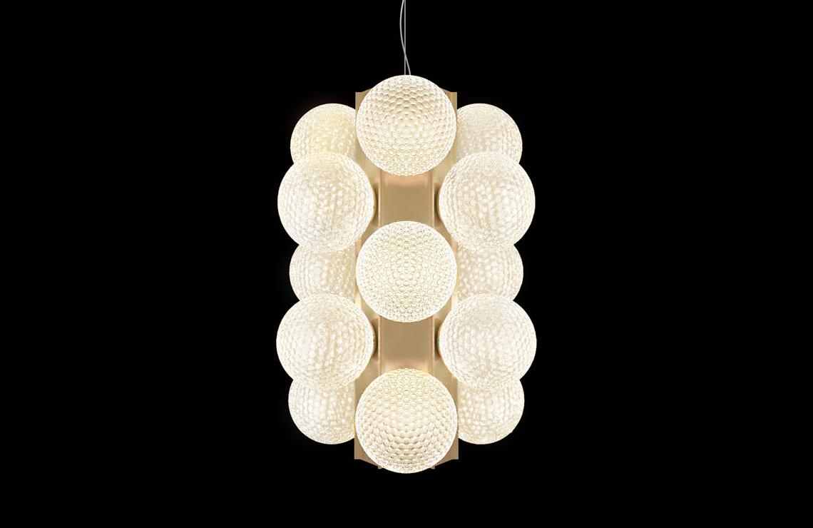 Barovier & Toso Lincoln – утонченный вертикальный подвесной светильник. Стеклянные сферы, расположенные по бокам центрального прямоугольного элемента, выполнены в традиционной венецианской технике «балотон»: такая обработка позволяет свету, исходящему изнутри, создавать уникальные эффекты. Корпус светильника, выполненный в цвете розовое золото, в нижней части содержит мощный светодиодный источник, испускающий луч света.