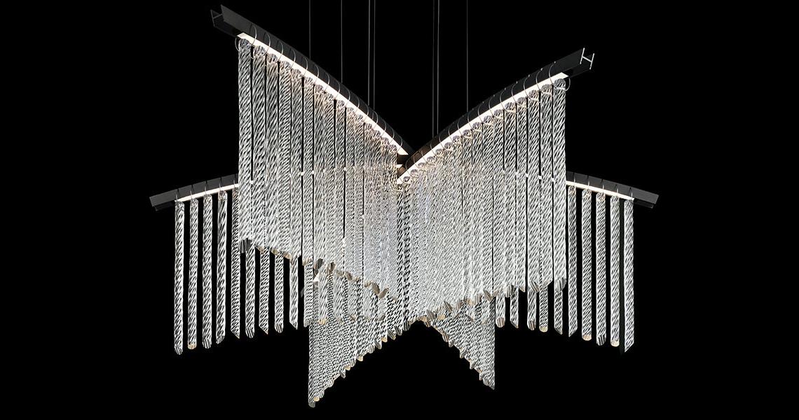Barovier & Toso Palmyra – очень легкий подвесной светильник, в основе которого – изогнутые линии, наложенные друг на друга. К анодированной стальной арматуре прикреплены скрученные подвески из стекловолокна, изготовленные в соответствии с муранскими традициями обработки стекла. Свет исходит от LED-ленты, укрытой в арматуре. Palmyra позволяет создавать различные пространственные комбинации: от «двумерной» версии (одна световая линия) до асимметричной модели с 4 линиями разной длины. По запросу также можно увеличивать диаметр и высоту светильника.