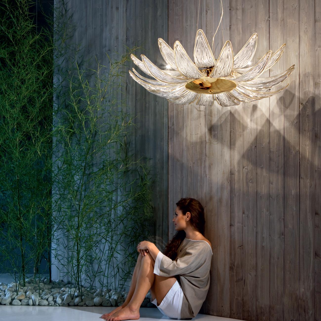 Уникальную по дизайну коллекцию предлагает и известный австрийский бренд Kolarz. Подвесная модель DALIA выполнена в виде огромного цветка, расположенного на основе, которая покрыта 24-каратным золотом. Лепестки изготовлены вручную из прозрачного муранского стекла. Модель комплектуется шестью лампами и может стать идеальным дополнением интерьера в стиле модерн и флора.