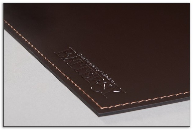 Темно-коричневый кожаный бювар с тиснением.