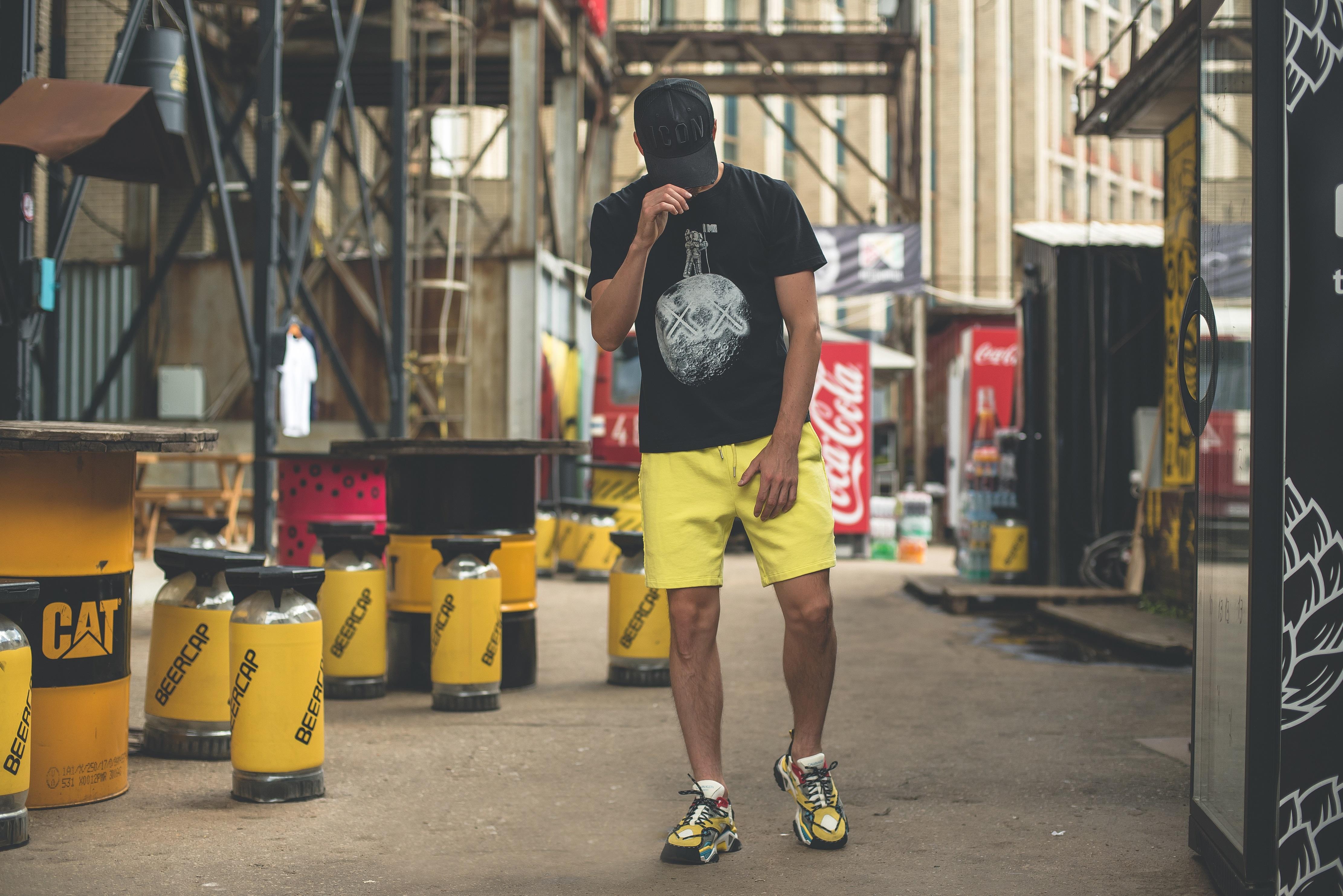 Яркий лук в желтых шортах в стиле спорт-кэжуал 2020 в сочетании с темным верхом.