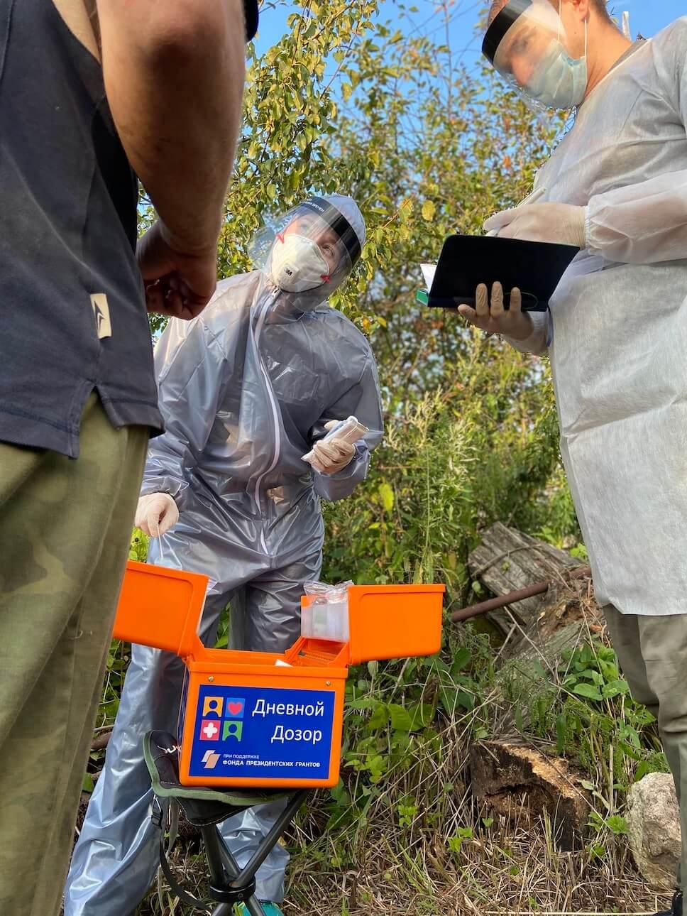 Многоразовый мембранный защитный комбинезон на сотруднике Дома Друзей, работа с пациентом