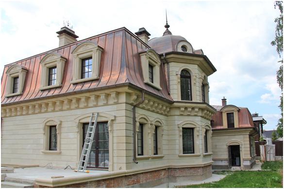 Фасад дома идёт облицовка бетоном и натуральным камнем