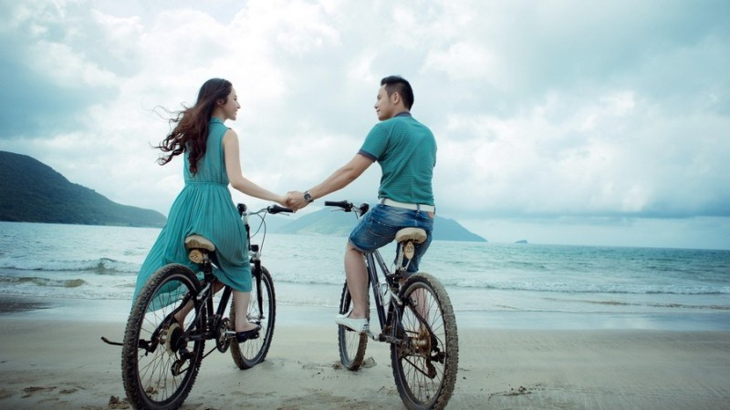 Пара на велосипедах на побережье моря