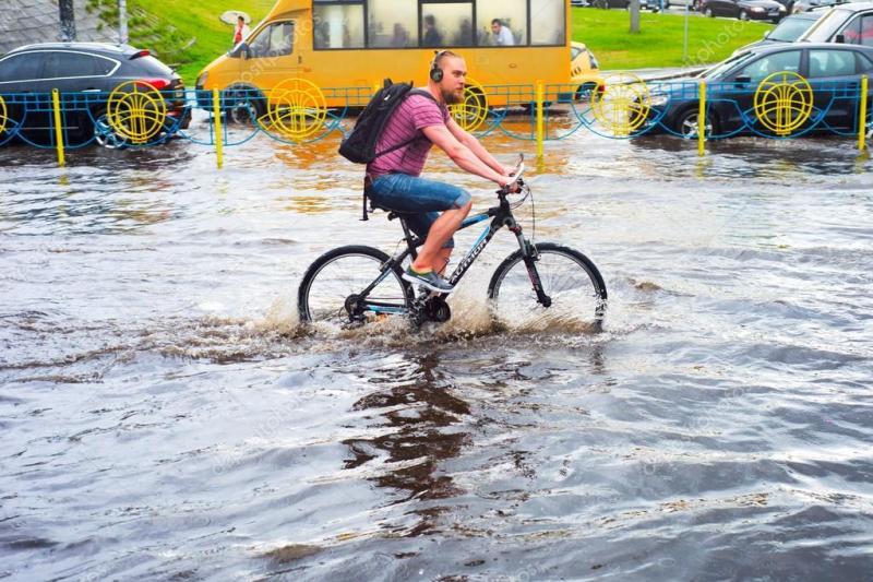 Велосипедист пересекает лужу