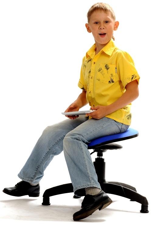 Мальчик в желтой рубашке сидит на танцующем стуле Фото
