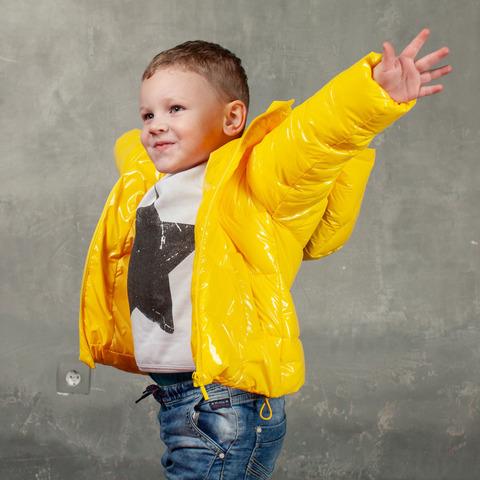 Демисезонная детская куртка желтого цвета из лаковой плащевки с нашивкой