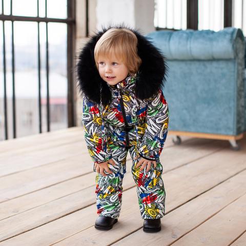 Детский зимний комбинезон с принтом  «Граффити» и опушкой из натурального меха черного цвета