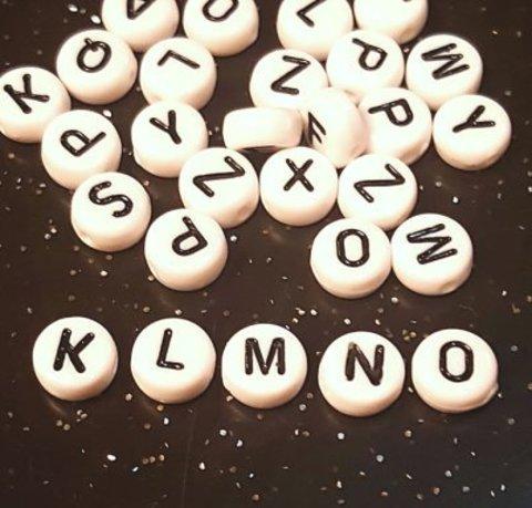 Бусина из белого акрила - буква «K»