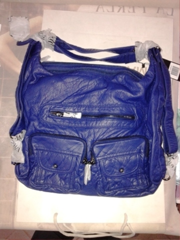 Синяя сумка рюкзак с двумя накладными карманами.