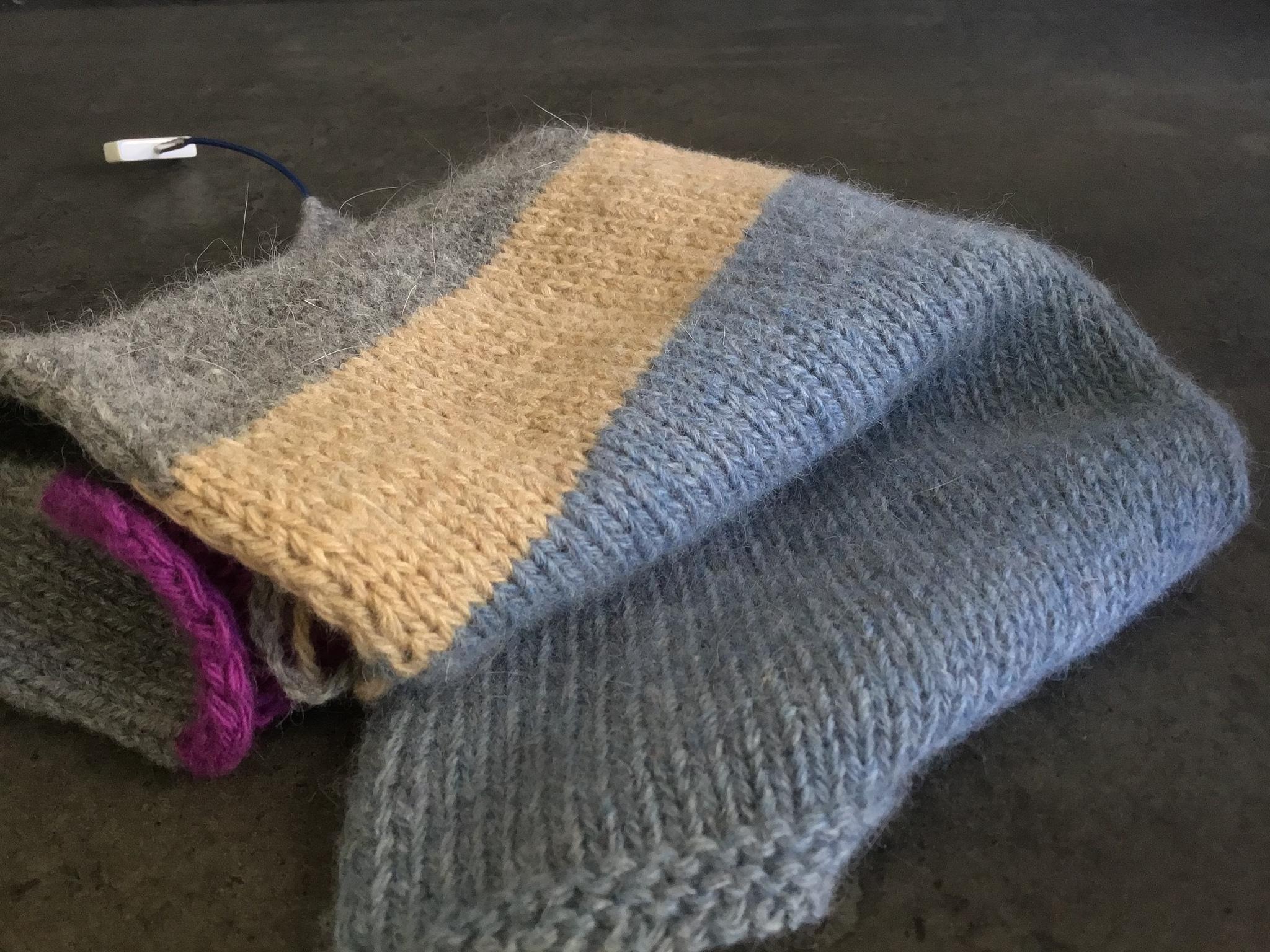 Образец Foxy, меринос с ангорой, связан в 4 нити на спицах 4,5 мм. Одна стирка. Толщина для очень тёплого свитера. Голубой и серый.