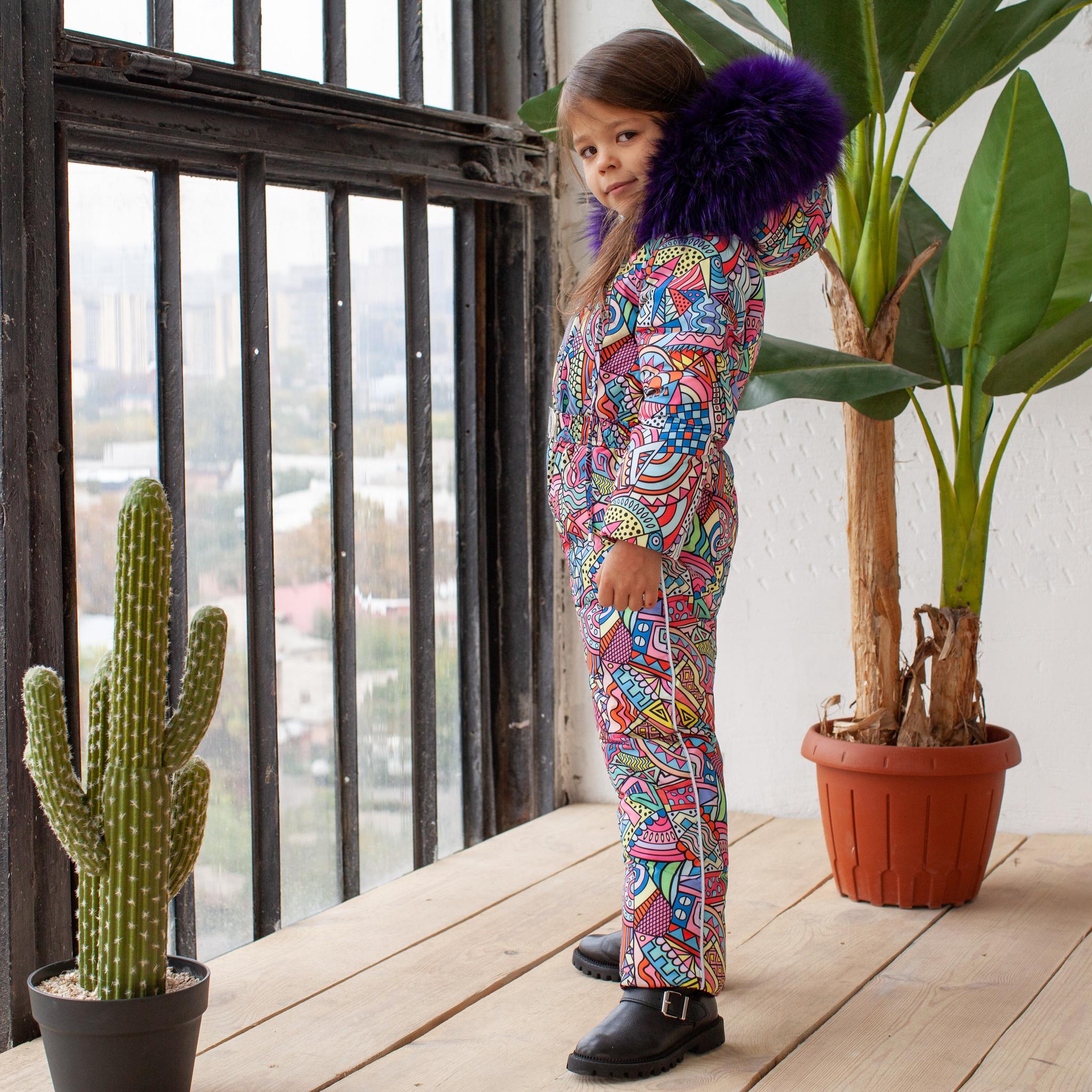 Детский зимний комбинезон с принтом  «Граффити» и опушкой из натурального меха фиолетового цвета