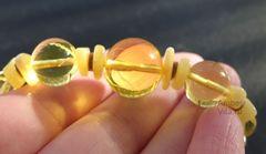 бусы из янтарных шаров на ладони в лучах солнца
